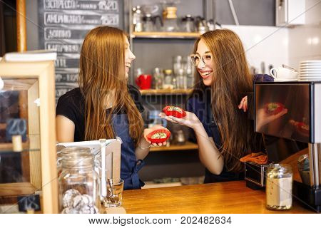 Two Happy Girls Baristas Holding Donuts In Their Hands