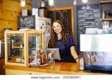 Cute Girl Barista Counting The Bill In The Coffee House On The Tablet