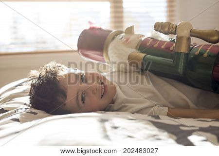 A Beauty child who holding a nutcracker in bed