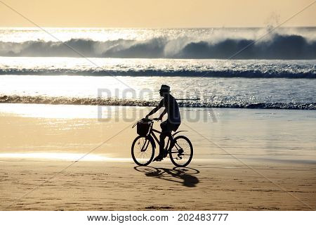 A girl on a bicycle is riding along the ocean at sunset. Bali Indonesia