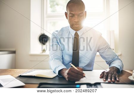 Young Businessman Signing Contracts At His Office Desk