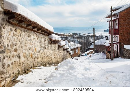 winter snow in traditional bulgarian balkan village with stone wall and houses