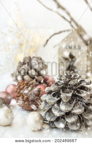 White Christmas decoration composition big pine cones scattered baubles shiny star wooden candle holder dry tree branches in background minimalist style