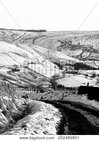 smow scene with small country road in yorkshire moor landscape going downhill with fields and stone walls
