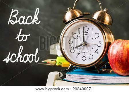 Stack of notebooks workbooks pads pencils supplies with alarm clock red apple on top. Back to school hand lettering on chalkboard. New studying year vintage style copy space.