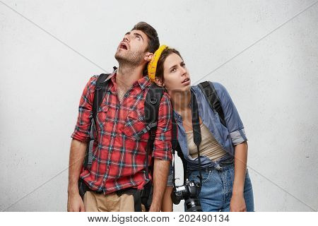 Studio Shot Of Young Man And Woman Travelers In Sensible Clothes Carrying Heavy Backpacks Leaning On