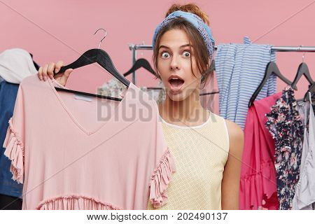Astonished Female With Wide Opened Mouth, Holding Hanger With Pink Dress, Being Surprised Of High Pr