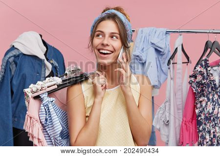 Stylish Young Female Shopaholic Speaking On Mobile Phone To Her Friend, Boasting About Her Purchases