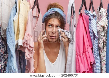Crying Woman Wiping Her Face With Clothes While Standing Near Her Wardrobe, Calling Her Friend, Comp