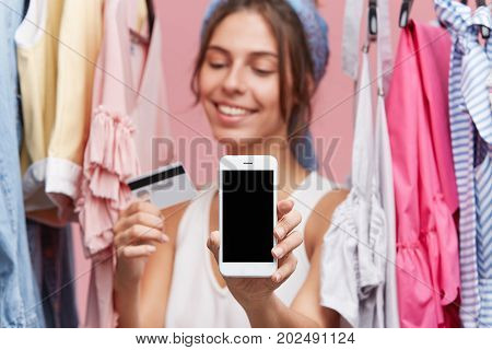 Female With Happy Expression Standing Near Rack With Clothes Over Pink Background, Keeping In Hands