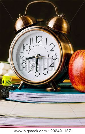Alarm clock and red apple on top of a stack of workbooks notebooks pads. Pencils pens eraser on desktop. Black chalkboard in the background. Back to school concept new studying year.