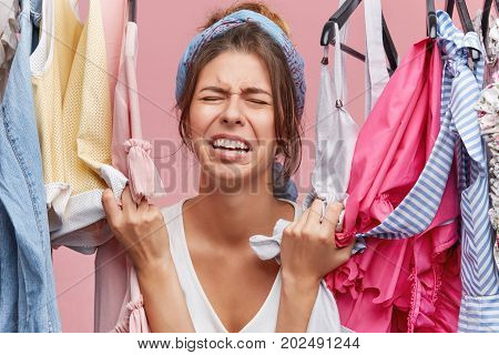 Stressed Unhappy Young European Female Touching Stylish Clothes And Crying Out Loud Because She Can'