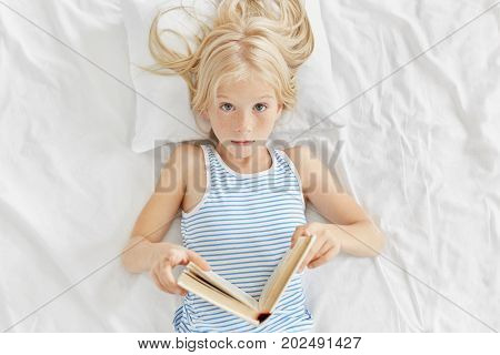 Astonished Girl Looking Surpsiely Into Camera, Keeping Book In Hands, Reading Interesting Stories Wh