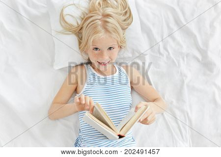 Indoor Shot Of Cheerful Adorable Little Girl With Blonde Hair Lying On White Pillow In Her Bedroom,