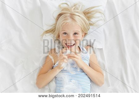Good Looking Freckled Girl Playing With Her Brother At Bed, Fighting With Pillows, Catching Feathers