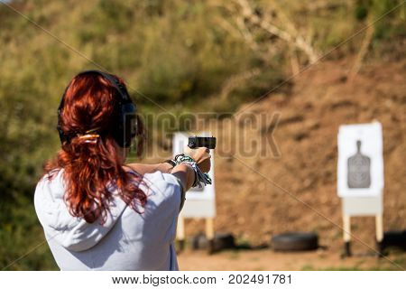 A Young Girl Holds A Pistol And Targets A Shot At A Shotgun, Headphones On The Head, A Big Burst Of