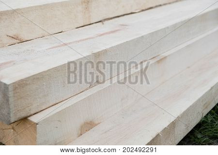 Stack of new wooden studs at a lumber yard warm color retro tone selective focus image.