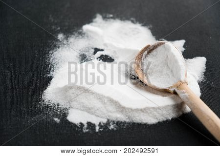 Spoonful of bicarbonate. Baking soda, Sodium bicarbonate, NaHCO3. wooden spoon on a black background.