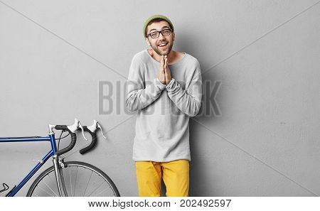 Fashionable Hipster Guy Begging For Something While Standing Against Grey Background Near Bicycle. Y