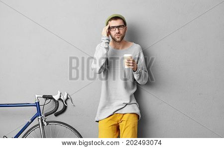 Studio Shot Of Young Bearded European Hipster In Hat And Eyeglasses Drinking Coffee In Disposable Pa