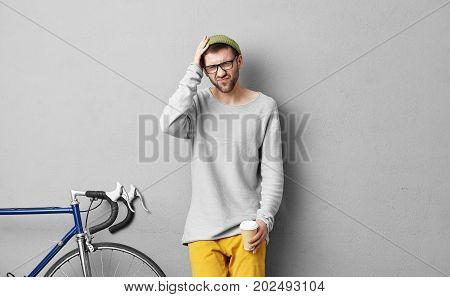 Lifestyle Portrait Of Fashionable Young Male With Beard Having Painful Look Because Of Headache, Sta