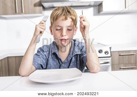 Little boy with bored grumpy expression sitting at a table in front of a large empty white bowl waiting for breakfast funny