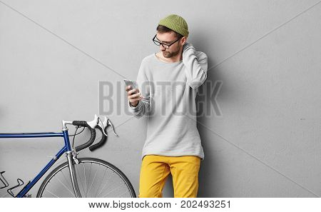 Unshaven Young European Guy Wearing Stylish Glasses And Hat Touching His Neck While Reading Importan