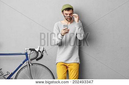 Picture Of Young Bearded Male Wearing Trendy Hat And Clothes Holding Eyeglasses While Reading Strang