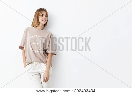Beautiful Young Female With Boobed Hair, Wearing Loose Shirt And White Trousers, Modeling Against Wh