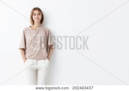 Attractive Young Female Model With Bobbed Hair, Wearing Stylish Clothes, Keeping Her Hands In Pocket