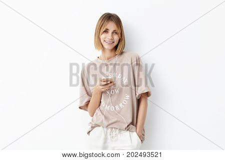 Smiling Good Looking Female Model With Bobbed Hairstyle Having Walk Alone, Using Earphones And Mobil