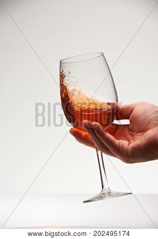 Holding red wine in glass and shake for tasting. Check quality of red wine