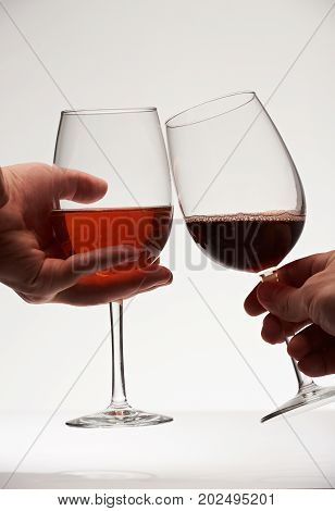 People making toast  with two red wine glasses. Close-up hands holding wine glasses and cheers