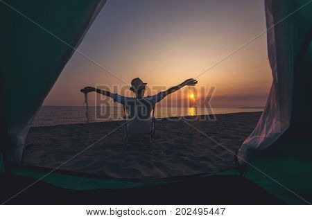 Camping on the beach sea. Woman on the beach sitting in front of the tent and watching the sunset