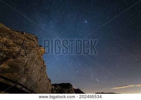 Night On The Alps Under Starry Sky And The Majestic Rocky Cliffs On The Italian Alps, With Orion Con