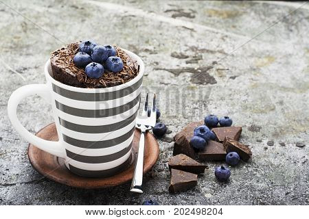 Healthy breakfast or snack. Chocolate mug cupcake with blueberries and chocolate chips in a gray striped ceramic mug on a gray stone background. Selective focus