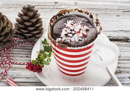 A mug cake for a festive New Year's Eve snack with red white sweets in a striped red white mug on a gray stone background with winter paraphernalia. Selective focus