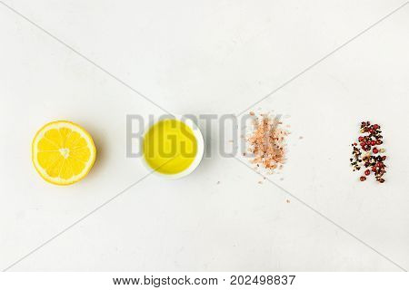 Flat lay of ingredients for vinaigrette sauce. Lemon olive oil Himalayan salt red black white pepper on white stone background. Cope space for text. Poster menu template. Minimalist.