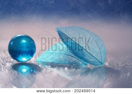 A glass blue ball and a transparent leaf skeleton on a glass table with reflection and a beautiful bokeh