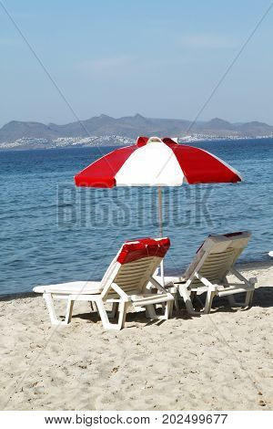 Red-white beach umbrella and chaise lounges on the beach of the island of Kos. Greece