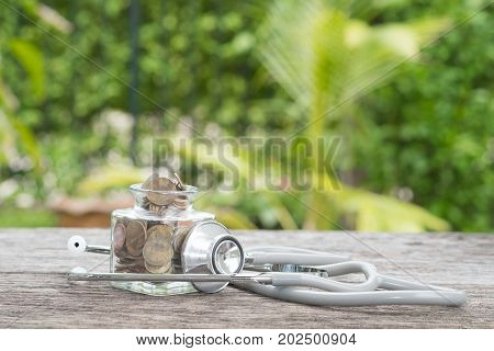 Stethoscope on bottle and coin on wooden background. Concept of financial planning for health care.