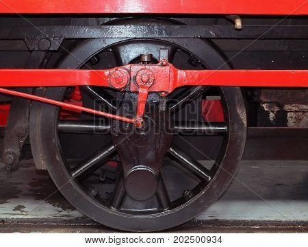 wheel of an old steam locomotive painted black with red coupling rods
