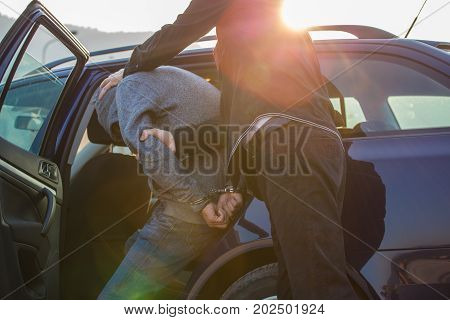 Arresting a thief a criminal a drug dealer with hands armed with police cuffs a thief disabled Two policemen lead him and lead him to the car