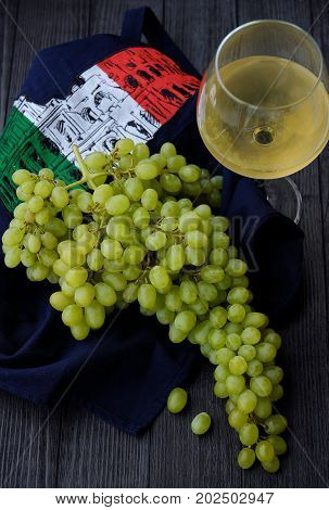 Green fresh grapes and wine in the Italian background