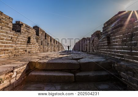 Tourist With Open Arms At The Great Wall Of China. The Great Wall Of China Is The World's Longest Wa
