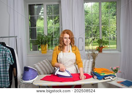 Housewife doing laundry and ironing. Foxy woman in home interior doing casual work.