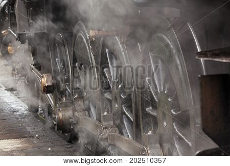 Close-up of steam train wheels with steam in the foreground and space for text.