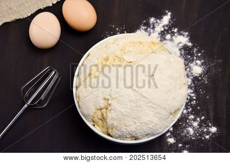 yeast dough in a Cup of flour on a black background eggs flour
