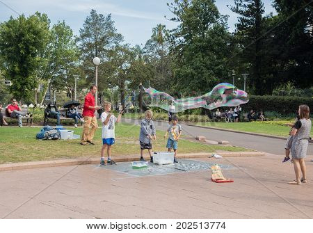 SYDNEY,NSW,AUSTRALIA-NOVEMBER 20,2016: Street busker and children playing with tri-string bubble wand and giant bubble in Hyde Park in Sydney, Australia.