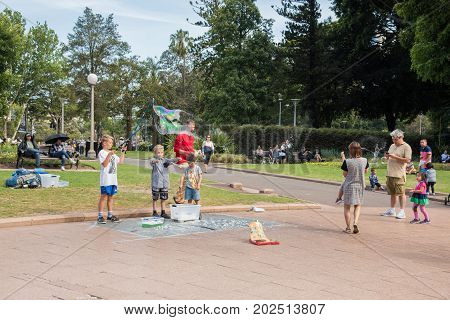 SYDNEY,NSW,AUSTRALIA-NOVEMBER 20,2016: Street busker and children playing with tri-string bubble wand and rainbow popped bubble in Hyde Park in Sydney, Australia.